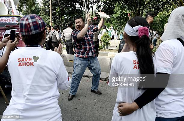 A man dances as he gathers with supporters of Jakarta's Christian governor Basuki Tjahaja Purnama better known by his nickname Ahok during his...