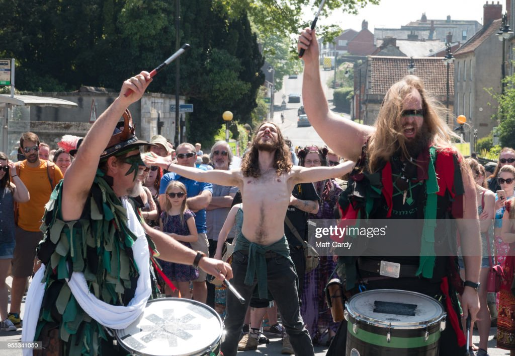 A man dances as the Pentacle Drummers perform as they wait for the Glastonbury Dragons to be paraded through the town as they take part in May Fayre and Dragon Procession in Glastonbury on May 6, 2018 in Somerset, England. To celebrate the arrival of summer, the Glastonbury Dragons, alongside Gwythyr Ap Greidal, the Summer King and the Winter King, Gwyn Ap Nudd, were paraded through the town to the lower slopes of Glastonbury Tor where the event was marked with a Beltane themed ceremony.