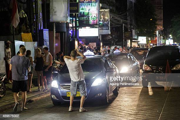 A man dances infront of a taxi on Legian Street during Australian 'schoolies' celebrations on November 26 2014 in Kuta Bali Indonesia This year...