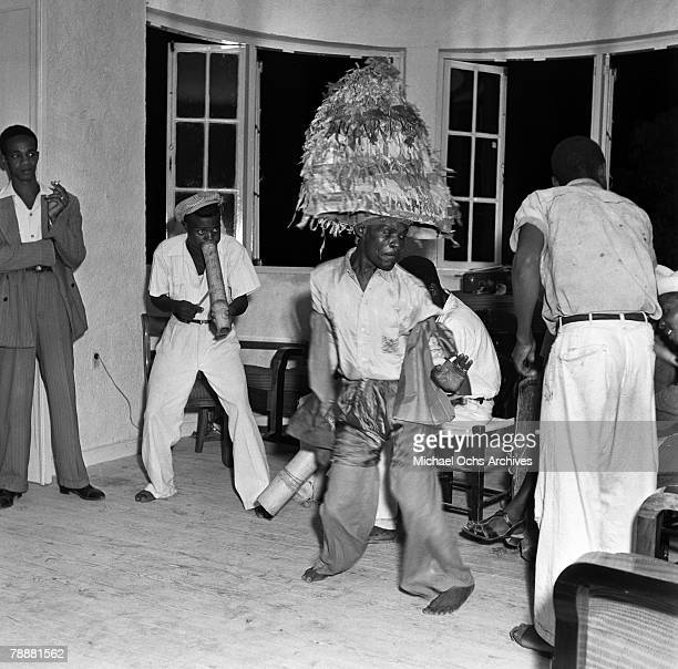 A man dances the kingly dance known as the Rabordage to the music of a vaccine at a party in 1946 in PortauPrince Haiti He is wearing a papiermache...