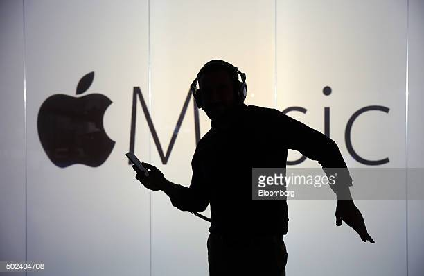 A man dances to music being streamed on his Apple Inc iPhone 6s whilst framed against a wall bearing the Apple music symbol in this arranged...