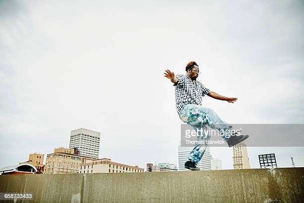 Man dancing along rooftop wall of building