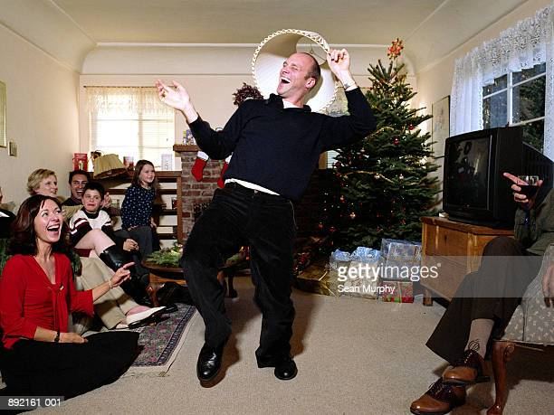 Man dancing around with lamp shade on head, surrounded by family