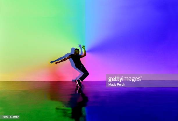 man dancing in abstract space with lots of colours around him - uitvoerende kunst voorstelling stockfoto's en -beelden