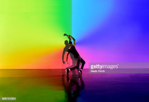 man dancing in an abstract space with lots of colours behind him - performing arts event stock pictures, royalty-free photos & images