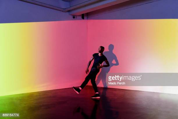 Man dancing in an warehouse space with lots of colours behind him