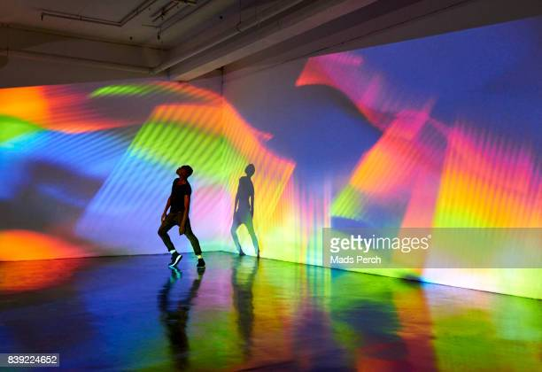 man dancing in front of large scale colourful projected image - arts culture et spectacles photos et images de collection