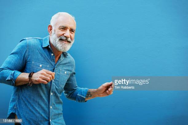 man dancing next to blue wall - freedom stock pictures, royalty-free photos & images
