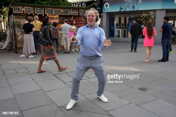 Man dancing on Oxford Street in London England United Kingdom Listening to music on his headphones this dancer joined in with another practicing his...
