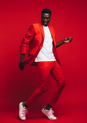 Man dancing on red background 1156449252