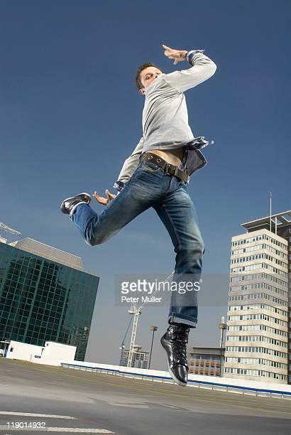 Man dancing on urban rooftop