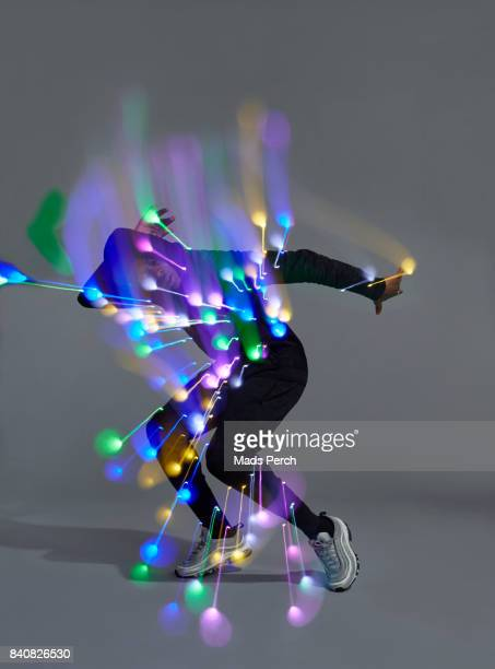 man dancing with led lights attached to him - actuación conceptos fotografías e imágenes de stock