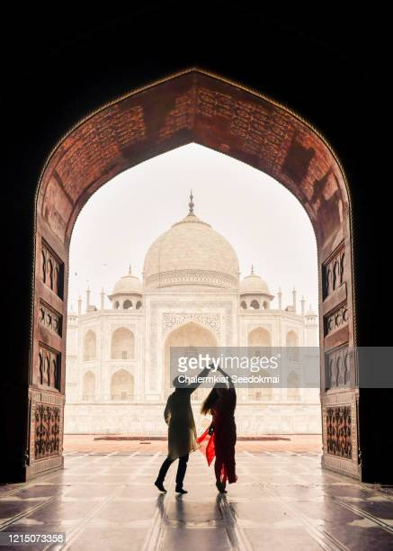 a man dancing with woman with the view of taj mahal in agra, india - agra stock pictures, royalty-free photos & images
