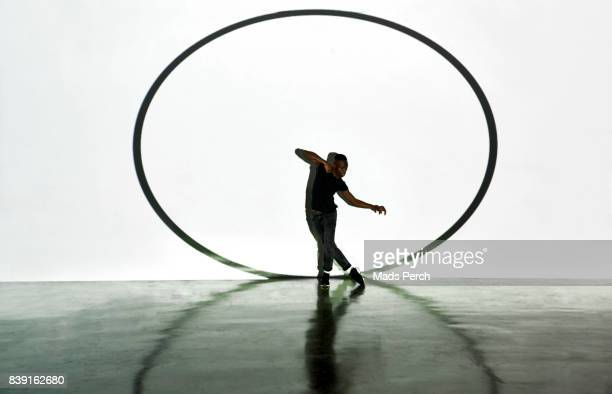 Man daning in large gallery space with projected circle behind him