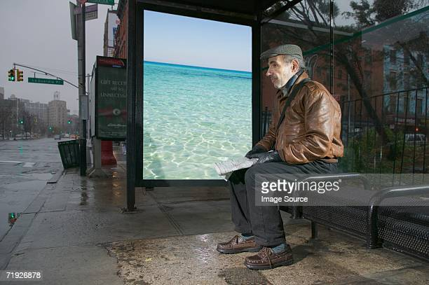 Man daydreaming in bus shelter