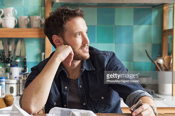 Man daydreaming in messy kitchen