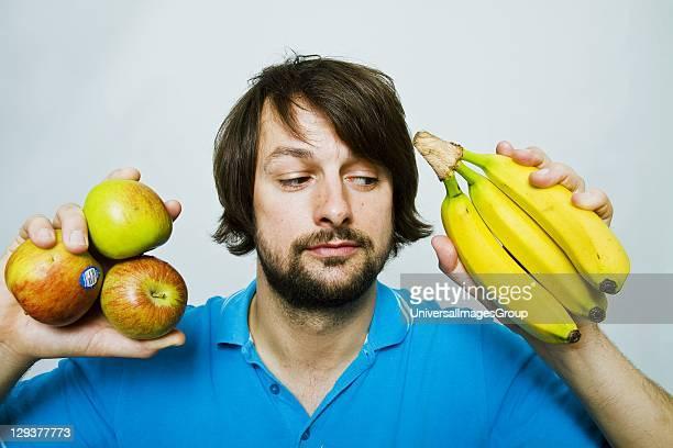 Man deciding whether to eat apple or banana