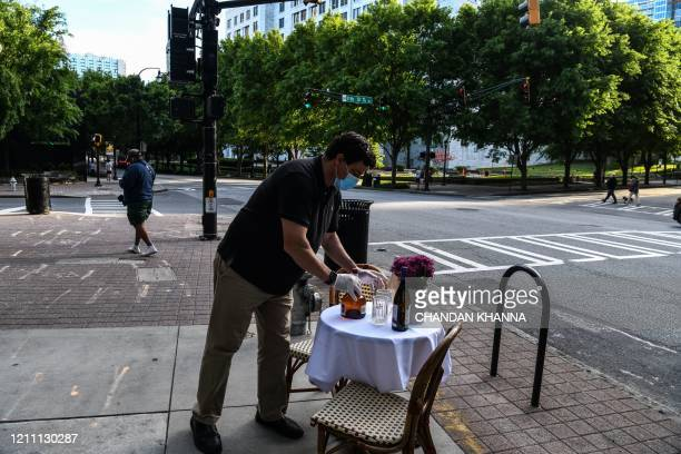 Man decorates a bistro table outside his restaurant amid the novel coronavirus pandemic in Atlanta, Georgia on April 27, 2020. - Some Georgia...