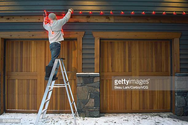 Man decorating house with Christmas lights