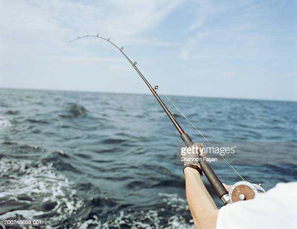 man deep sea fishing, rear view,close-up of arm - big game fishing stock photos and pictures