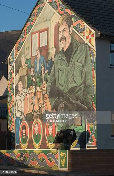 Man delievering coal to residents of Beechmount in west Belfast, walks past a mural dedicated to IRA volunteers 07 December 2004. The British and...