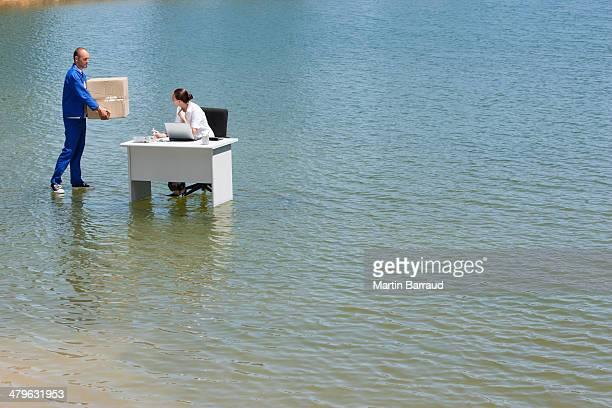 Homme proposer Boîte en carton de femme au bureau sur l'eau