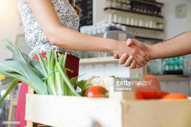 Man delivering crate of vegetables to shopkeeper