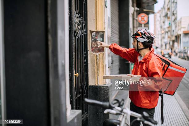 man delivering food and looking for right apartment - ringing doorbell stock pictures, royalty-free photos & images