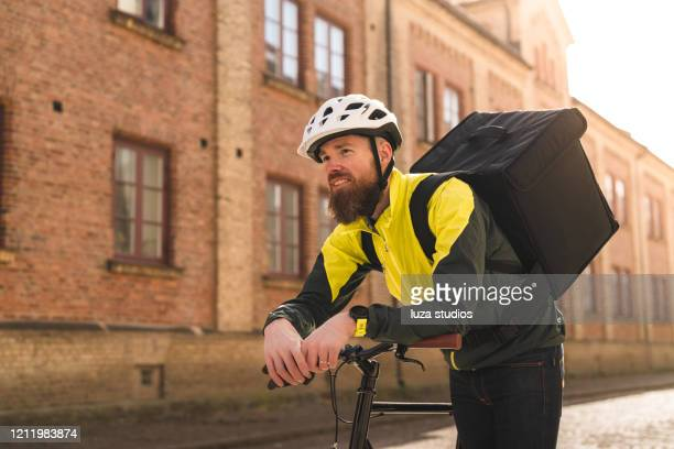 man delivering food by bike in the city - medium shot stock pictures, royalty-free photos & images