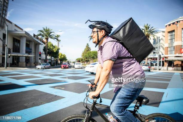 man delivering food on bicycle in busy city - bicycle messenger stock pictures, royalty-free photos & images