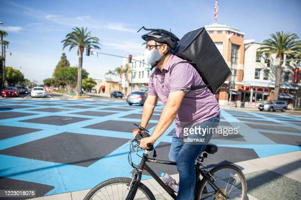 man delivering food on bicycle wearing a mask - adamkaz stock pictures, royalty-free photos & images