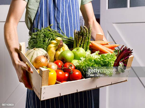 man delivering fruit and vegetable box. - fruit stock pictures, royalty-free photos & images