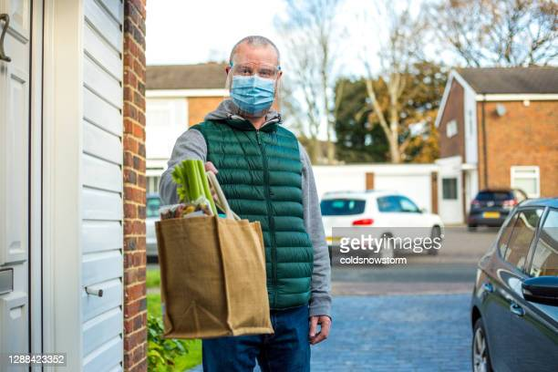 man delivering groceries to vulnerable seniors during covid-19 pandemic - fragility stock pictures, royalty-free photos & images