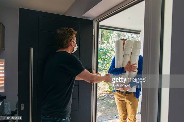 man delivering huge pile of toilet rolls to customer in mask - a helping hand stock pictures, royalty-free photos & images