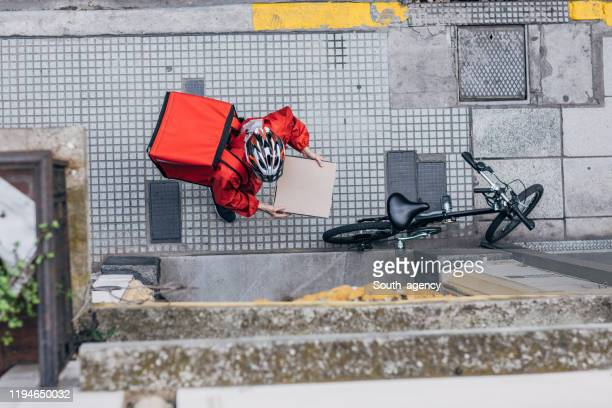 man delivering pizza in city - home delivery stock pictures, royalty-free photos & images
