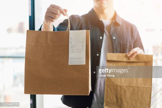 man delivering takeaway food at the front door - food delivery foto e immagini stock