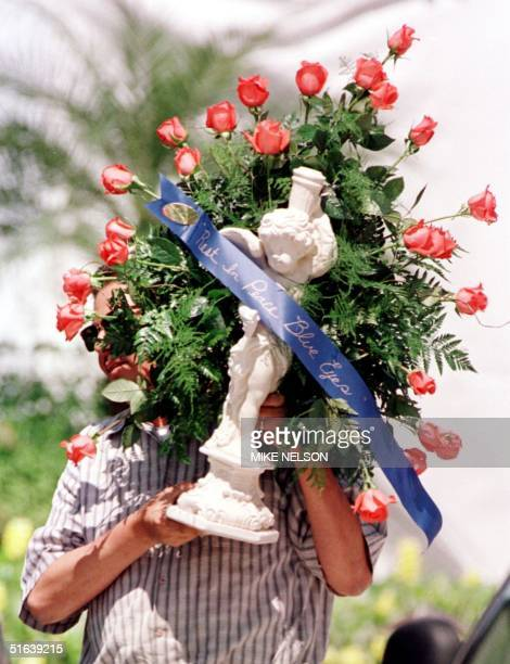 A man delivers a bouquet of flowers with a ribbon that says Rest In Peace Blue Eyes to the Good Shepard Catholic Church in Beverly Hills 20 May where...