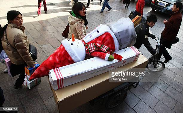 A man delivers Christmas decorations at a market on December 19 2008 in Beijing China A large number of Christmas decorations destined to the Western...