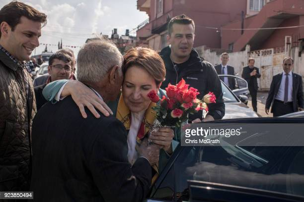 A man delivers flowers to IYI Party Chairman Meral Aksener during a stop on February 24 2018 in Reyhanli Turkey Meral Aksener and party members...
