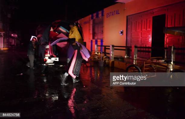 A man delivers mats to a temporary shelter at a primary school during heavy rains caused by Hurricane Karina in Tecolutla Veracruz state Mexico on...