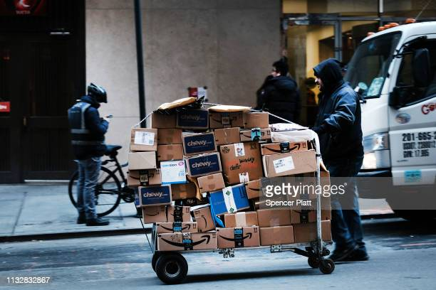 A man delivers packages along a street in midtown Manhattan on February 28 2019 in New York City New numbers released today by the Commerce...