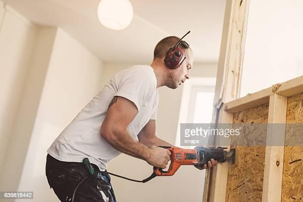 Man demolishing and rebuilding walls