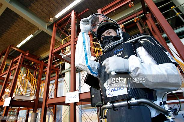 Man demonstrates the Hybrid Assistive Limb work-assist robot suit, developed by Cyberdyne Inc. In the New Energy and Industrial Technology...