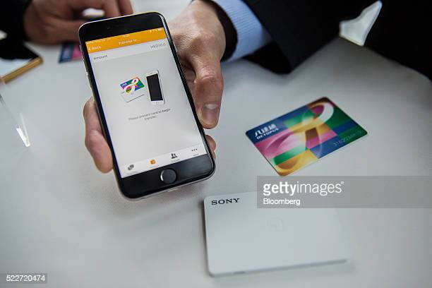 A man demonstrates the O ePay mobile payment service operated by Octopus Cards Ltd a subsidiary of MTR Corp using an Apple Inc iPhone and an octopus...