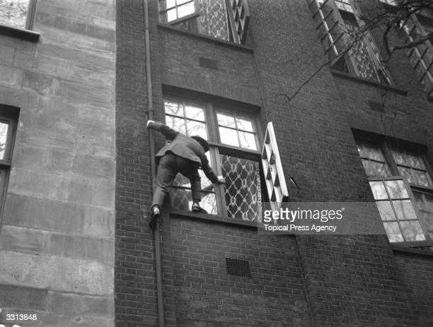 A man demonstrating how a cat burglar works