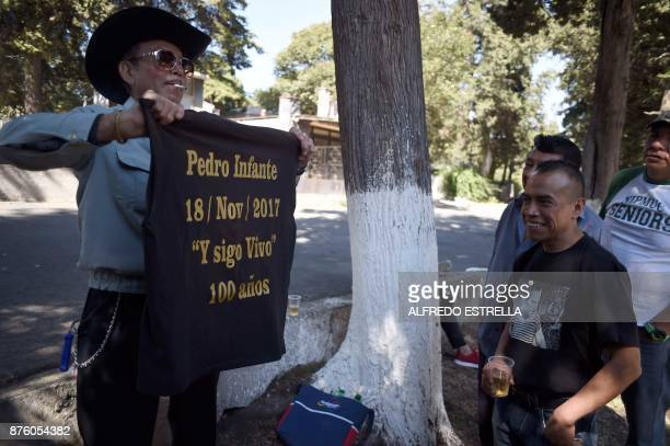 A man depicted Mexican singer and actor Pedro Infante shows a tshirt to visitors during the 100th Anniversary of his birth at the Panteon Jardin in...