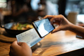 Man depositing check by phone in the restaurant