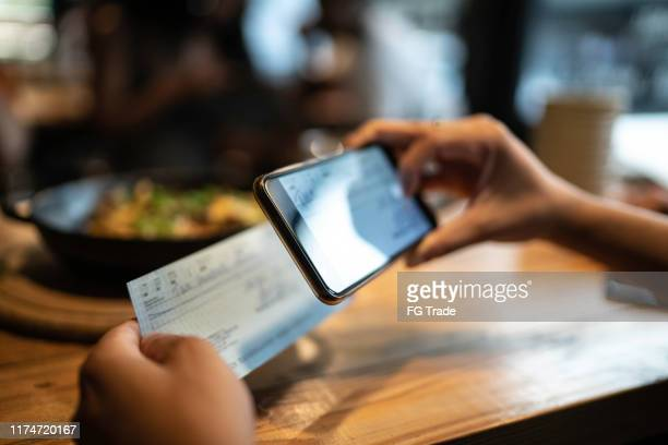 man depositing check by phone in the restaurant - portable information device stock pictures, royalty-free photos & images