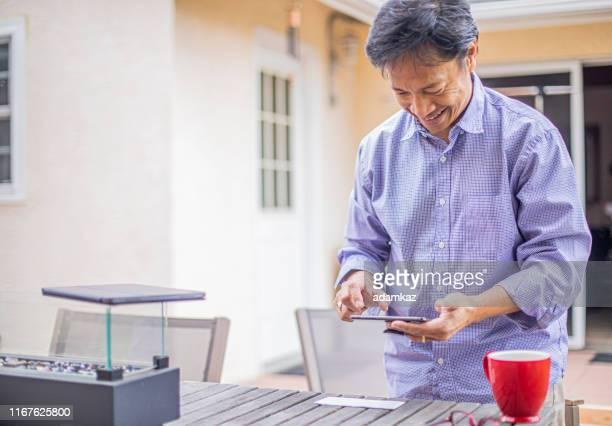 mann hinterlegt schecks mit smartphone - einzahlungsbeleg stock-fotos und bilder
