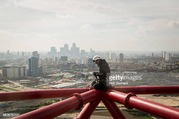 A man derigs abseiling equipment on the 1145 metre high ArcelorMittal Orbit tower at the Olympic Park on April 5 2014 in London England The Queen...
